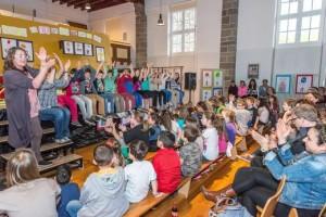 Trommel-Event in Schul-Aula: begeisternd spielende Kinder und beeindruckte Eltern